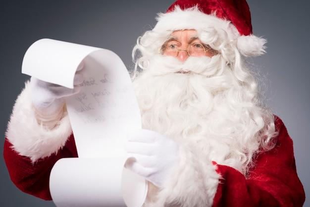 Weihnachtsmann liest eine wunschliste Kostenlose Fotos