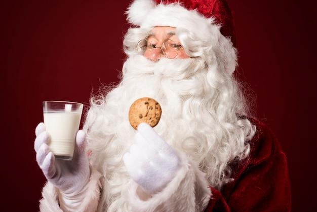 Weihnachtsmann mit einem keks und einem milchglas Kostenlose Fotos