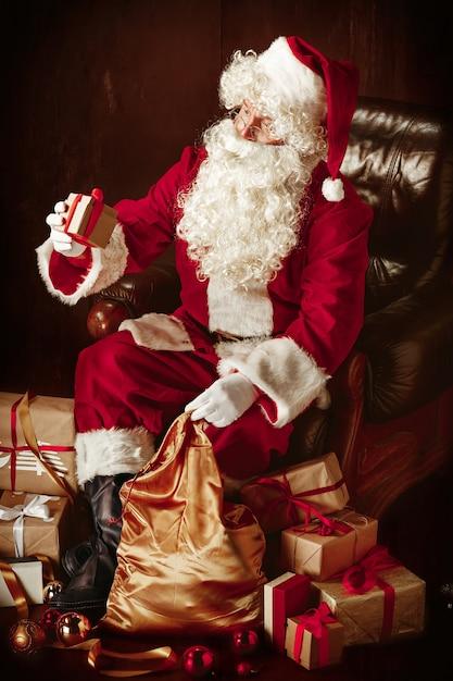 Weihnachtsmann mit einem luxuriösen weißen bart, einer weihnachtsmannmütze und einem roten kostüm, das mit geschenken sitzt Kostenlose Fotos