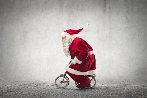 Weihnachtsmann mit einem winzigen fahrrad Premium Fotos