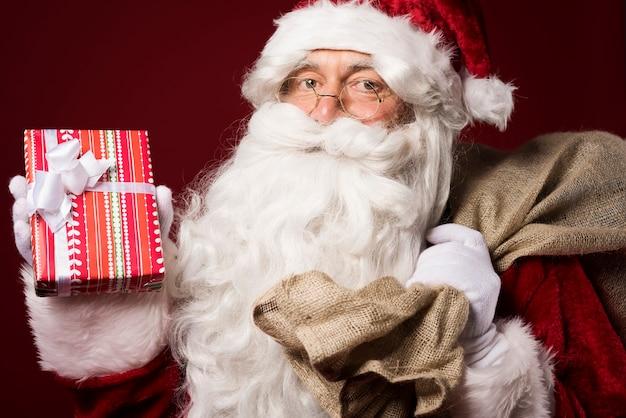 Weihnachtsmann mit einer geschenkbox auf rotem hintergrund Kostenlose Fotos