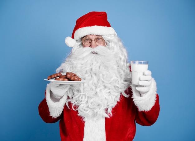 Weihnachtsmann mit keks und milch bei studioaufnahme Kostenlose Fotos