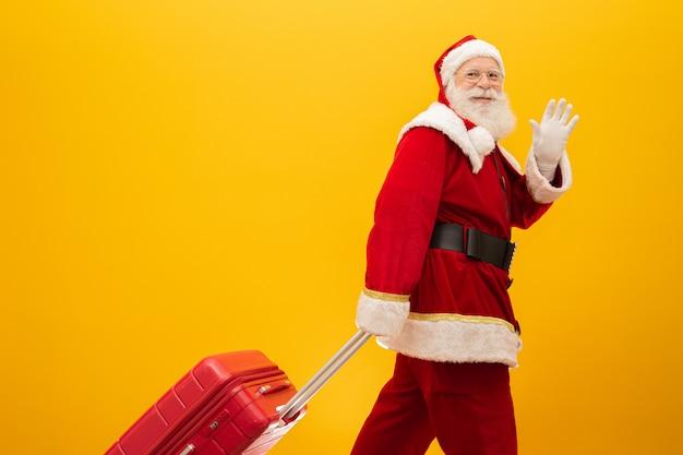 Weihnachtsmann mit seinem koffer. neujahrs-reise-konzept Premium Fotos