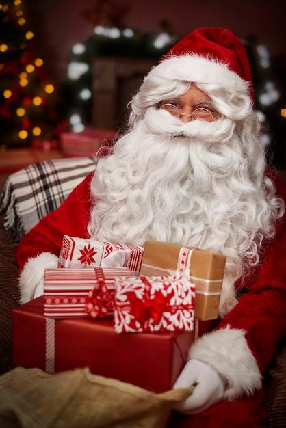 Weihnachtsmann mit stapel von weihnachtsgeschenken Kostenlose Fotos