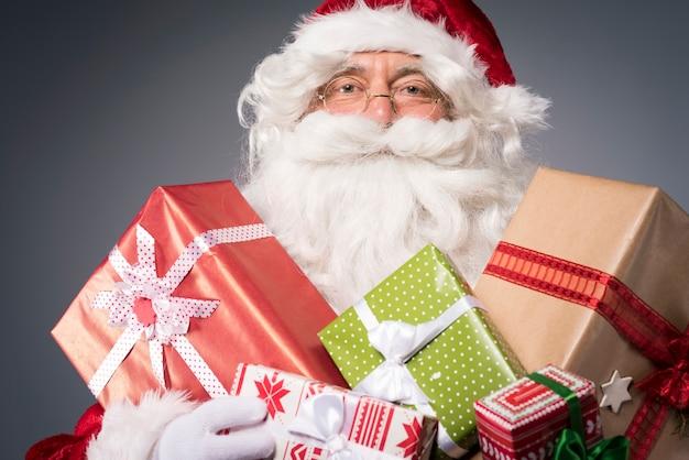 Weihnachtsmann mit vielen geschenkboxen Kostenlose Fotos