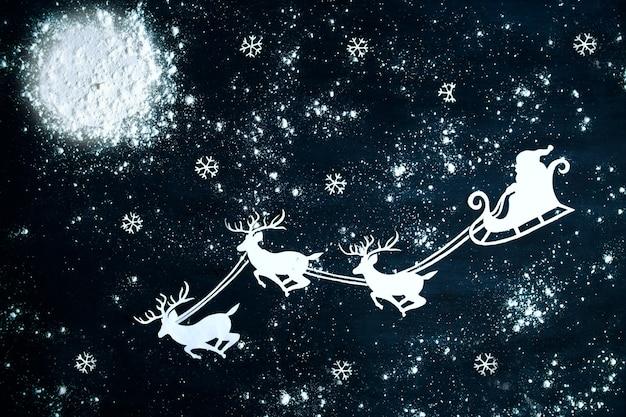 Weihnachtsmann und rentier fliegen durch den nachthimmel. weihnachtshintergrund. Premium Fotos
