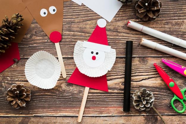 Weihnachtsmann- und rentierstützen mit tannenzapfen; filzstift und schere auf schreibtisch aus holz Kostenlose Fotos