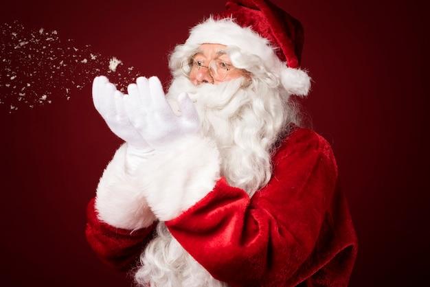 Weihnachtsmann weht schnee Kostenlose Fotos