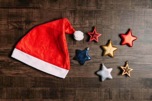 Weihnachtsmannmütze mit metallischen sternen auf hölzernem hintergrund. Premium Fotos