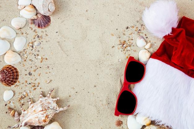 Weihnachtsmütze und brillen auf dem sand in der nähe von muscheln. urlaub. neujahrsurlaub. Premium Fotos