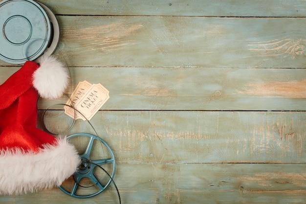 Weihnachtsmütze und kinoobjekte auf hölzernem hintergrund Premium Fotos