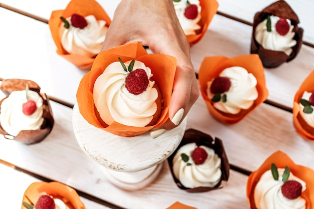 Weihnachtsmuffins mit sahne und beeren in oranger einzelverpackung Premium Fotos