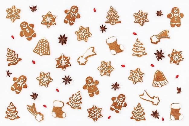 Weihnachtsmuster von lebkuchenplätzchen und gewürzen auf weißem hintergrund. flach liegen. Premium Fotos