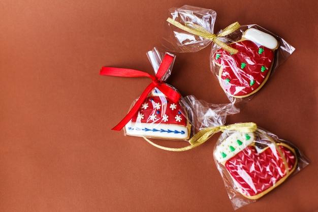 Weihnachtsneujahrsfeiertagshintergrund, rote lebkuchenplätzchen und kegel auf dunkelroter tabelle. kopieren sie platz Premium Fotos