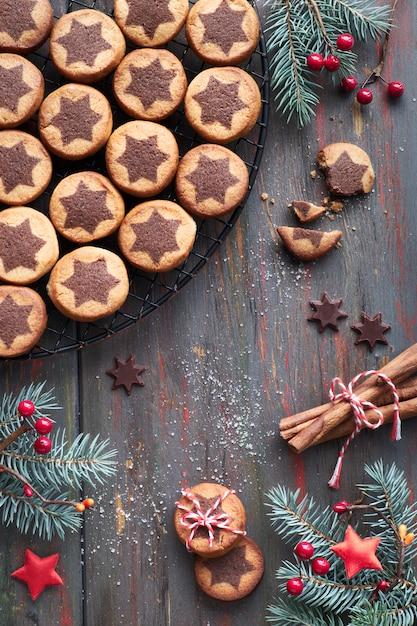 Weihnachtsplätzchen mit schokoladensternmuster auf abkühlendem gestell mit gewürzen und den verzierten tannenzweigen Premium Fotos