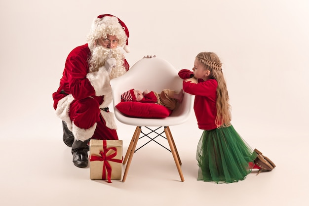 Weihnachtsporträt des niedlichen kleinen neugeborenen, hübsche jugendlich schwester, gekleidet in weihnachtskleidung und weihnachtsmann mit geschenkbox Kostenlose Fotos