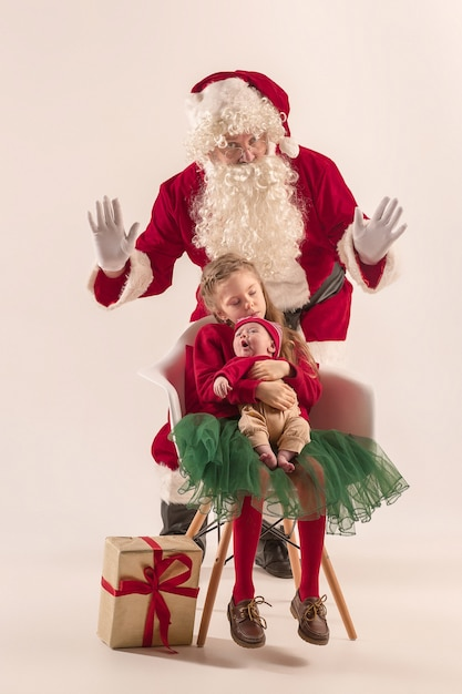 Weihnachtsporträt des niedlichen kleinen neugeborenen mädchens, der hübschen jugendlich schwester, gekleidet in weihnachtskleidung und mann, der weihnachtsmannkostüm und -hut, studioaufnahme, winterzeit trägt. das weihnachts-, feiertagskonzept Kostenlose Fotos