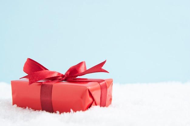 Weihnachtsrote geschenkbox mit rotem bogen auf schnee, kopienraum. Premium Fotos