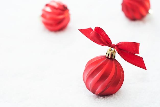 Weihnachtsroter flitter lokalisiert auf schnee. winter-grußkarte. Premium Fotos