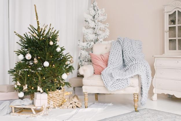 Weihnachtsschlitten mit geschenken und einer decke, ein stuhl mit kissen in der nähe des weihnachtsbaumes im wohnzimmer, dekoriert für das neue jahr Premium Fotos