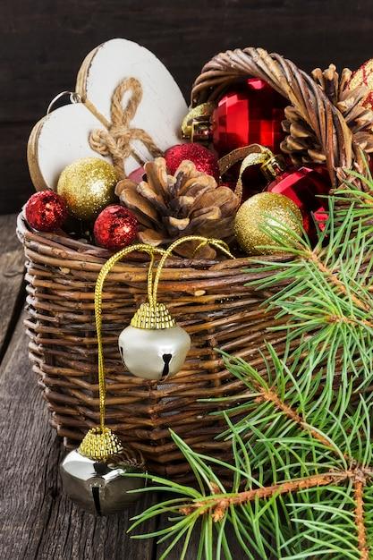 Weihnachtsschmuck in einem korb auf einer holzoberfläche Premium Fotos