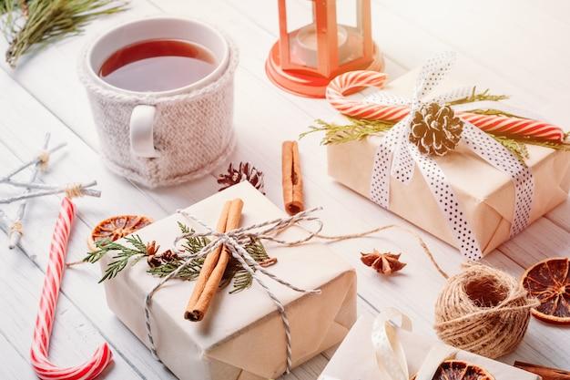Weihnachtsschmuck mit geschenkboxen, tannenzapfen und einer tasse tee Premium Fotos