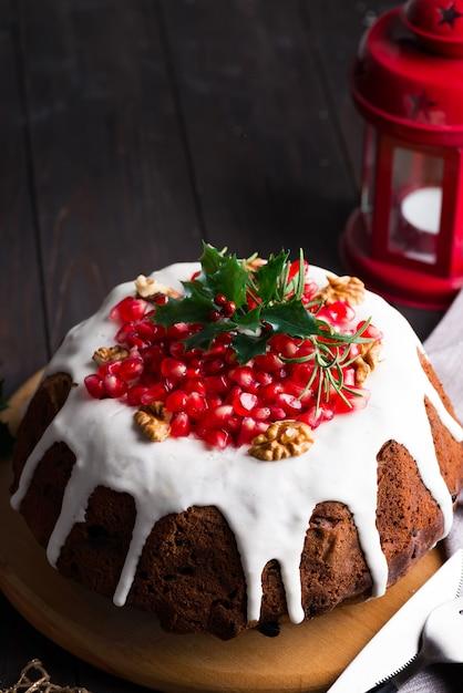 Weihnachtsschokoladenkuchen mit weißen zuckerglasur- und granatapfelkernen auf einer hölzernen dunkelheit mit roter laterne und poinsettia Premium Fotos