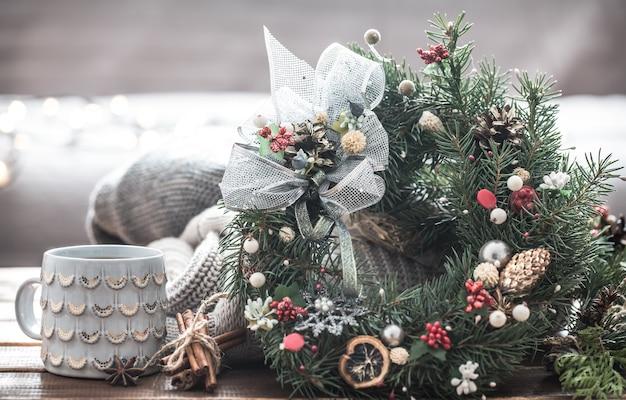 Weihnachtsstillleben von weihnachtsbäumen und -dekorationen, festlicher kranz vor dem hintergrund von gestrickten kleidern und schönen tassen, weihnachtsgewürze Kostenlose Fotos