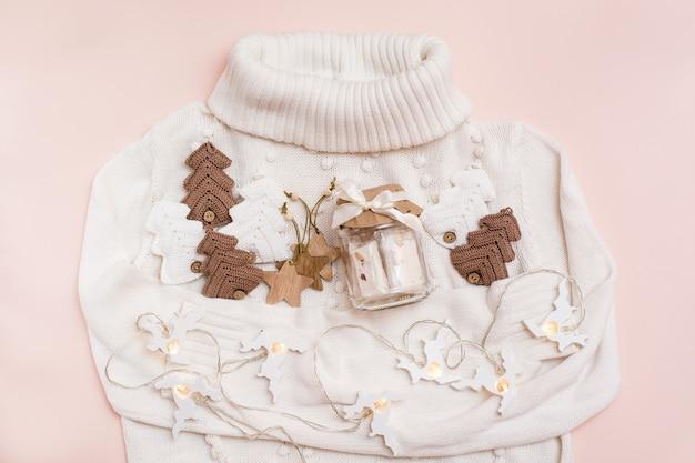 Weihnachtsstimmung. glas mit paste, gestrickten tannen, holzspielzeug und einer hirschgirlande auf einem weißen pullover. handwerksdekor. kein verlust Premium Fotos