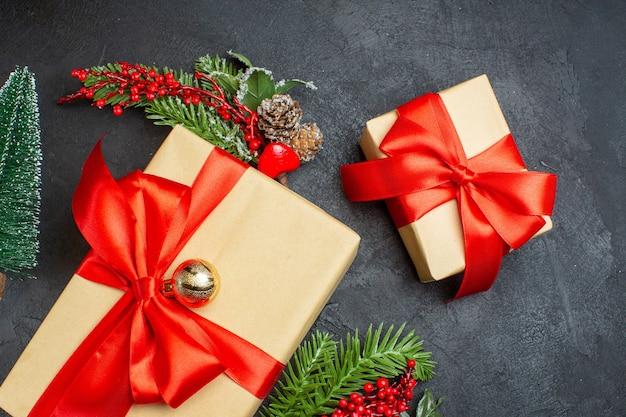 Weihnachtsstimmung mit schönen geschenken mit bogenförmigem band und tannenzweigdekorationszubehör auf dunklem hintergrund Kostenlose Fotos