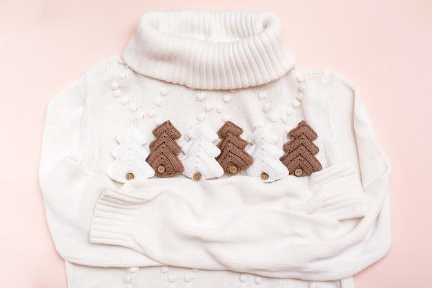 Weihnachtsstimmung. weißer pullover umarmt gestrickte tannen. handwerksdekor. kein verlust Premium Fotos