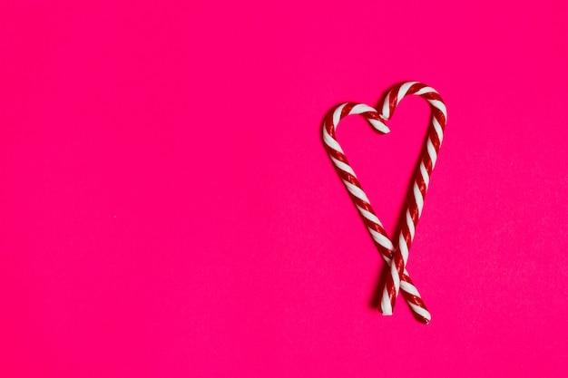 Weihnachtssüßigkeitsherz auf rosa hintergrund Premium Fotos