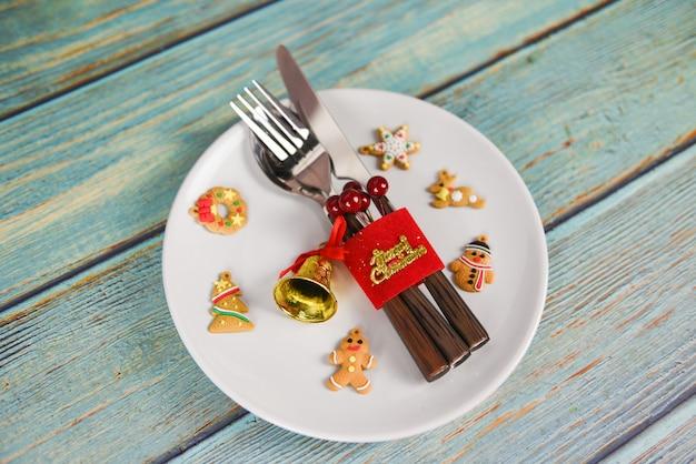 Weihnachtstabellengedeckdekoration mit gabellöffel und -messer auf hölzernem speisetische der weißen platte Premium Fotos