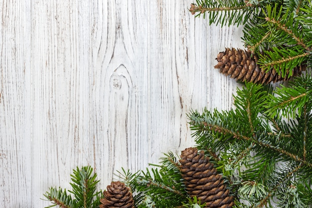 Weihnachtstannenbaum mit kiefernkegeln auf einem hölzernen brett Premium Fotos