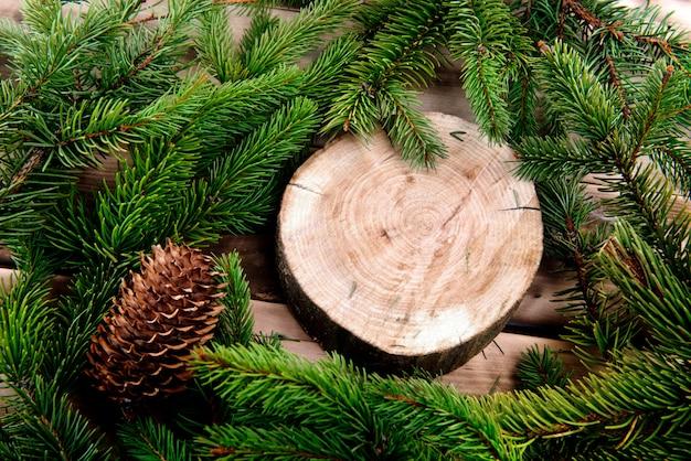 Weihnachtstannenbaum und runder hölzerner schnitt auf naturholz Premium Fotos