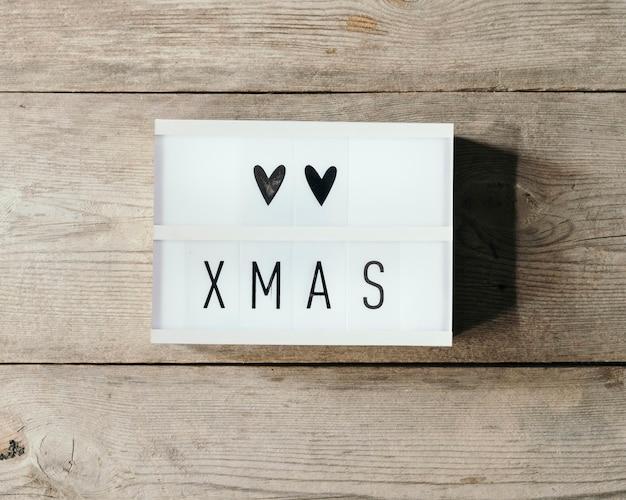 Weihnachtstext in led-tafel mit hölzernem hintergrund Kostenlose Fotos