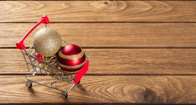 Weihnachtsverzierungsbälle auf miniaturwarenkorb über dem holz für netzfahne Premium Fotos
