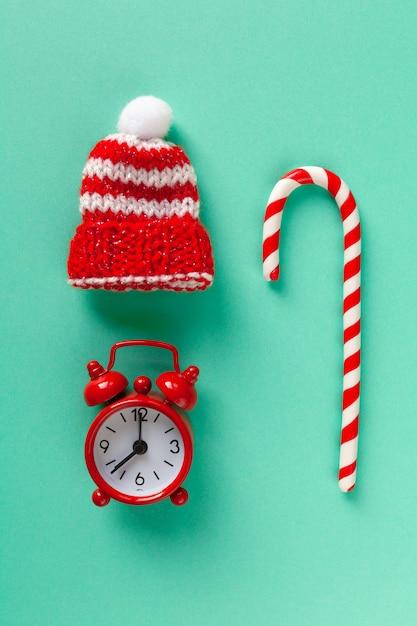 Weihnachtszuckerstange, -uhr und -hut auf pastelltürkishintergrund. Premium Fotos