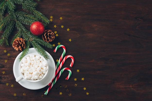 Weihnachtszusammensetzung auf dunklem hintergrund mit süßigkeit Premium Fotos