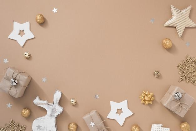 Weihnachtszusammensetzung. feld mit geschenken, handwerk und goldenen dekorationen auf beige pastellhintergrund. Premium Fotos