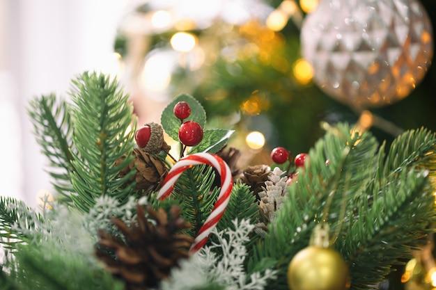 Weihnachtszusammensetzung mit kiefernblättern, kiefernkegeln, stechpalmenbällen, zuckerstange und ball Premium Fotos