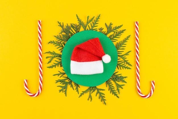 Weihnachtszusammensetzung mit nadelbaumzweigen auf gelbem papierhintergrund. runder rahmen von christbaumzweigen und dekorationen mit platz für text. draufsicht. neujahrskonzept Premium Fotos