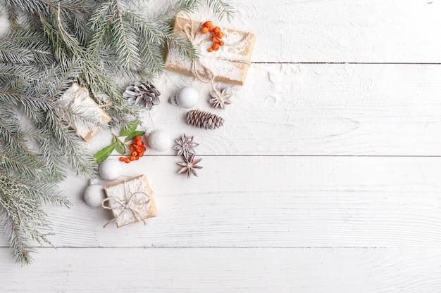 Weihnachtszusammensetzung mit rahmen von tannenzweigen, von weihnachtsdekorationen und von kiefernkegeln. flachgelegt, draufsicht Premium Fotos
