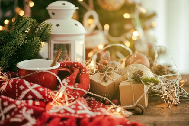 Weihnachtszusammensetzung mit roter schale schokolade, schal, laterne, sternblinker und bällen Premium Fotos
