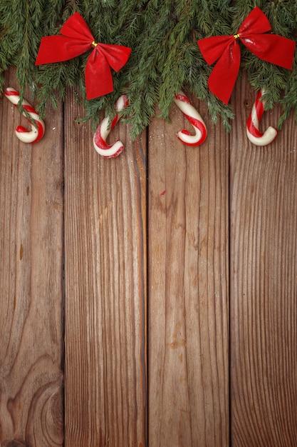 Weihnachtszusammensetzung von baumasten, von süßigkeiten und von dekorationen auf hölzernem hintergrund. ansicht von oben. kopieren sie platz. Premium Fotos
