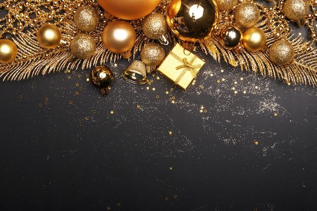 Weihnachtszusammensetzung von goldenen weihnachtsspielwaren und von dekorationselementen auf einem schwarzen hintergrund. Premium Fotos