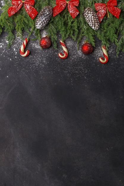 Weihnachtszusammensetzung von nadelbäumen, von dekorationen und von bonbons auf dunklem hintergrund. flach liegen. draufsicht natur-neujahrskonzept. kopieren sie platz. Premium Fotos