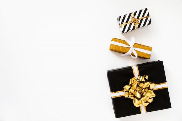Weihnachtszusammensetzung. weihnachtsgeschenke, schwarzes und goldenes packpapier auf weißem hintergrund Premium Fotos