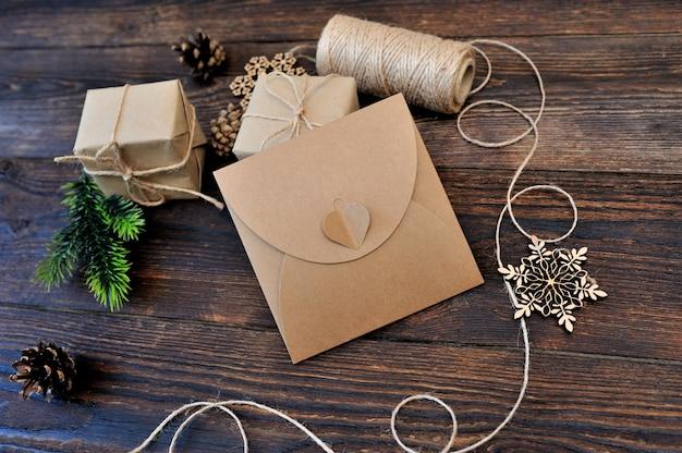 Weihnachtszusammensetzungssatz geschenkkraftpapierkästen, textilspielwaren und seil auf hölzernem hintergrund Premium Fotos