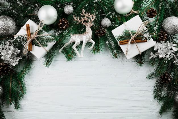 Weihnachtszweig mit silbernen rotwild und anwesenden kästen Kostenlose Fotos